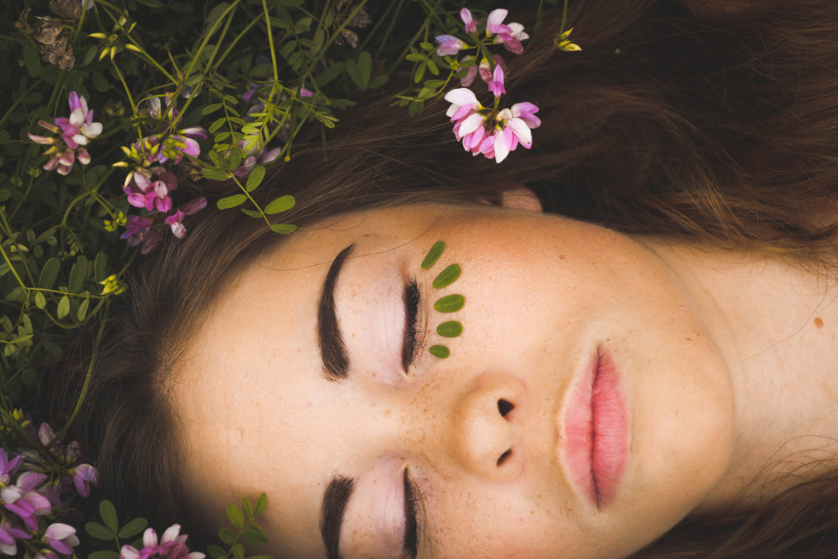 ragazza distesa sul prato e con make up con cosmetici biologici o naturali