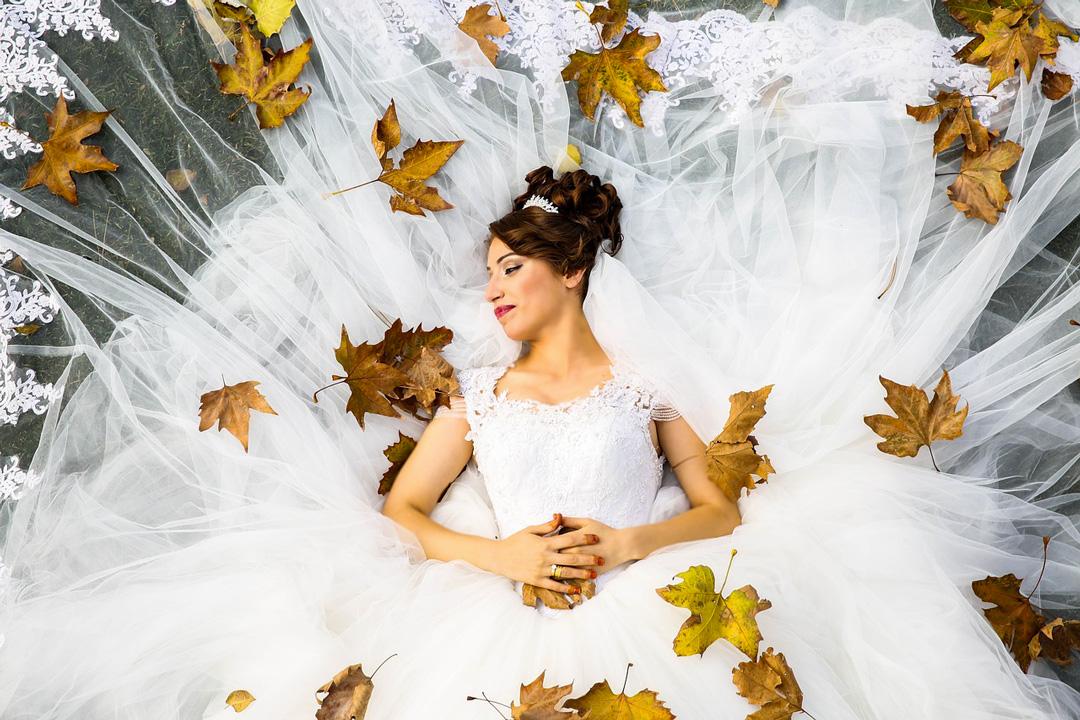 abito da sposa circondato da foglie di quercia essicate
