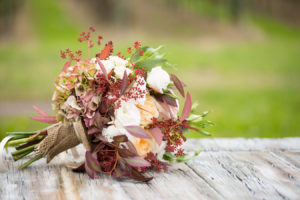 bouquet della sposa con rose e ortensie adagiato su tavolo in legno