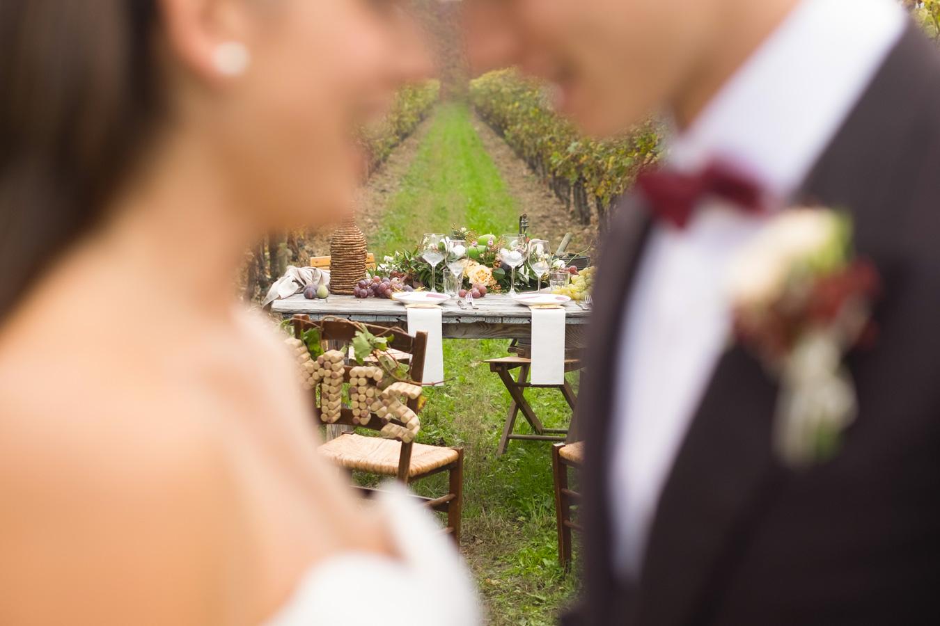 sposi che si guardano sorridendo e sullo sfondo il tavolo sposi in mezzo ai filari della vigna