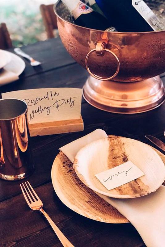 piatti in legno disposti su tavola apparecchiata e a fianco un bicchiere in metallo colo rame
