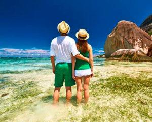 coppia sposi abbracciati e con cappello di paglia e vestiti verde e bianco che guardano l'orizzonte in piedi nel mare