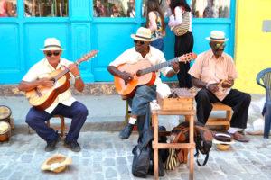 uomini anziani di Cuba che suonano la chitarra seduti su uno sgabello sulle strade di l'Havana