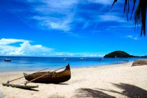 vecchia canoa di legno sulla spiaggia del Madagascar e sullo sfondo il mare con altre barche e un'isola