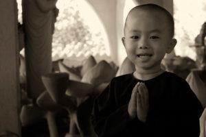 bambino asiatico che sorride e con le mani giunte in preghiera