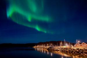 aurora boreale in Norvegia e sullo sfondo case tipiche norvegesi illuminate