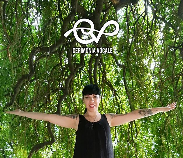 cantante cristina verderio in canotta nera che apre le braccia con sfondo i rami cascanti di un grande albero verde