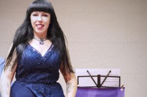 cantante Cristina Verderio in abito blu con leggio e partiture