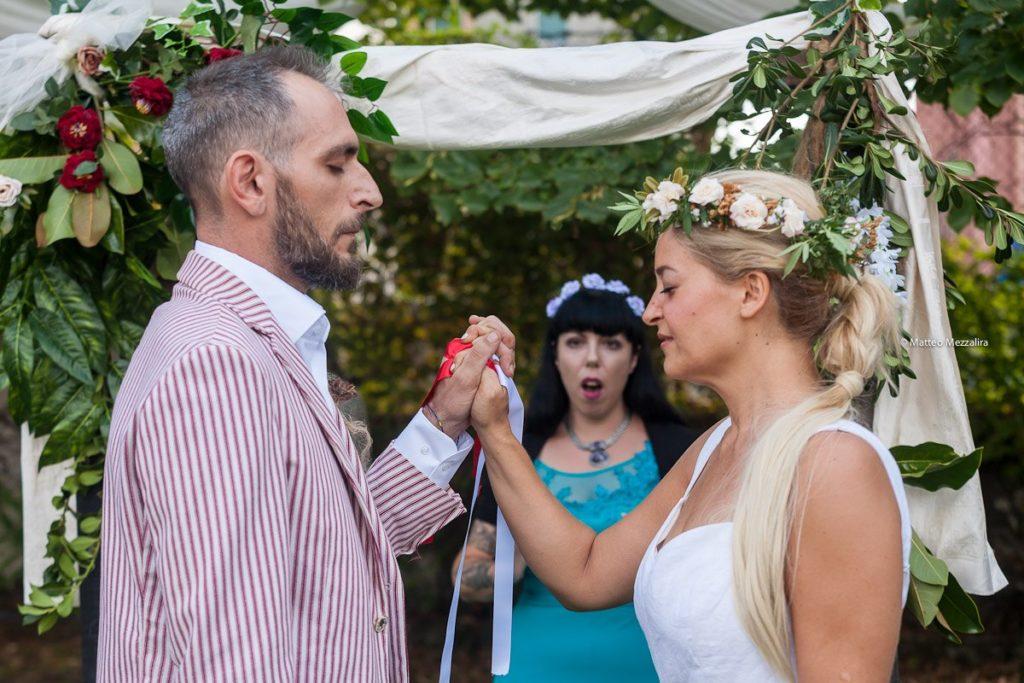 cerimonia di sposi che mani congiunte e occhi chiusi e cantante solista che anima la cerimonia in abito azzurro